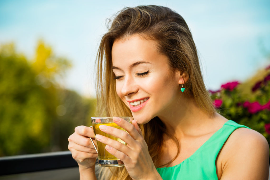 Happy Woman Drinking Green Tea Outdoors