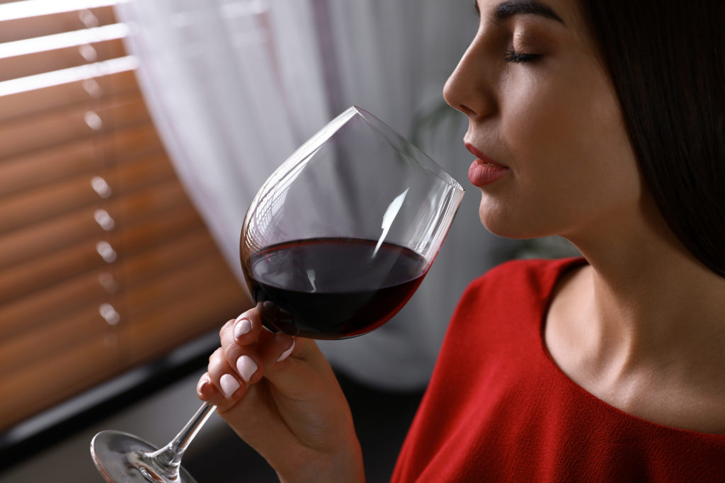 Beautiful Young Woman With Glass Of Luxury Red Wine Indoors, Closeup View. Space For Text