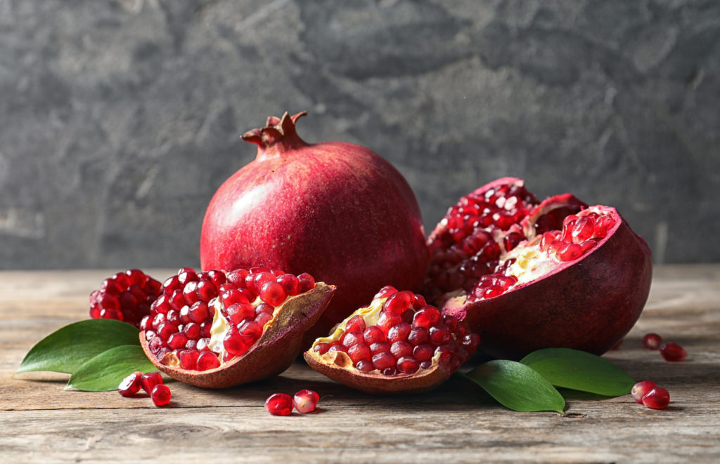 Ripe Pomegranates And Leaves On Table Against Grey Background. Space For Text