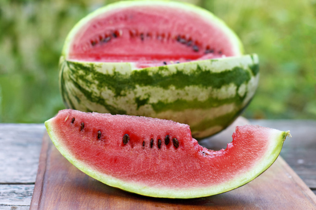 Ripe Watermelon Cut Into Slices On A Wooden Board